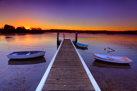 moorings: Little boats moored to a jetty at sunset.This is a quiet cove on the Brisbane Waters, Central Coast Australia Stock Photo