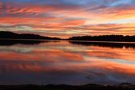 Sunrise and the sky became on fire and mirror reflections in the beautiful Narrabeen Lakes   Sydney, Australia photo