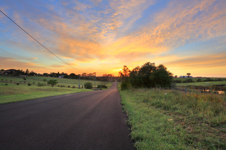 vista: Country road, farms and paddocks at sunrise morning.  Focus to foreground
