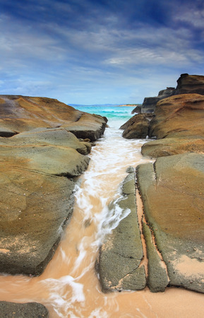 crevice: The ocean washes through a rock crevice.  Soldiers Beach, NSW, Australia.  Nice motion in the water contrasts the steadfastness of the rocks. Stock Photo