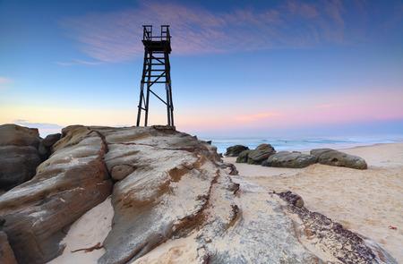 A bird sits on the shark tower at Redhead Beach, NSW Australia at dawn photo