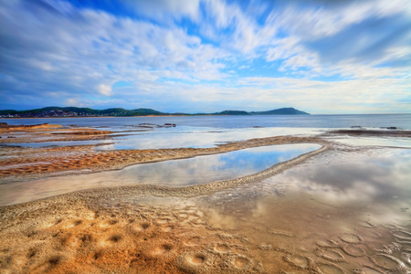 tides: Terrigal Haven, looking towards Terrigal and Wamberal, NSW Australia.  Water reflections and the beginnings of crater erosion. Motion  Focus to foreground  Long exposure 17sec