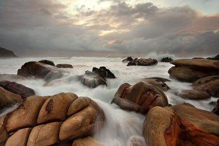 overrun: The ocean surges over well weathered rocks at Forresters Beach NSW Australia