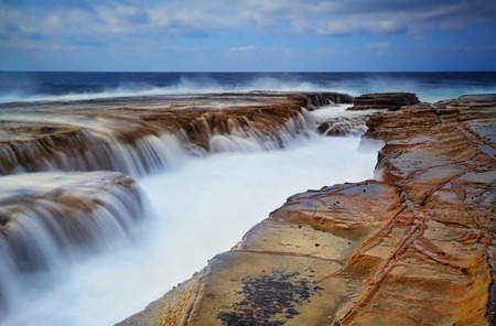 gallons: Gallons of surging ocean waves overflow into a deep eroded rock ravine
