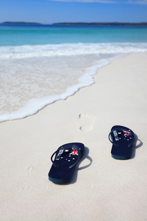 Australian flag thongs on the beach with footprints leading into the ocean.  Holiday, vacation, travel, leisure, unwind