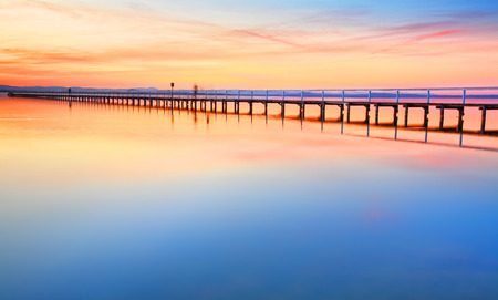 the long lake: Magnificent colours in the sky, pink towards the north and red towards the south, at idyllic Long Jetty Central Coast, Australia