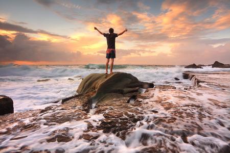 Tiener jongen staat op een rots onder woelige oceaan zeeën en snelstromend water bij zonsopgang verering, lof, schil, Adenture, eenzaamheid, het vinden van vrede onder lifes turbulente tijden overwinnen van tegenspoed Motion in water Stockfoto