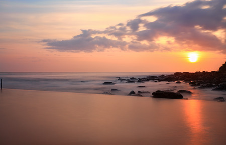 destress: A tranquil view over the pool to the ocean at sunrise, NSW, Australia.  Long exposure