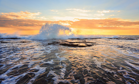 australia landscape: Sunrise splash in the shape of a wave  and water flow at Narrabeen rock shelf at high tide Stock Photo