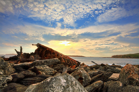woe: The setting sun highlights and backlights the rusting twisted metal remains of the SS Minmi that tragically shipwrecked in Botany Bay Sydney in 1937. Stock Photo
