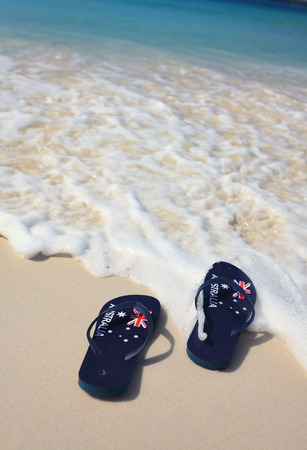 Patriotic Aussie thongs featuring Australian flag on the beach. Banque d'images