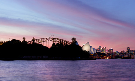 An awesome pink and red sunset sky over beautiful Sydney Harbour, Opera House, Harbour Bridge and CBD Australia
