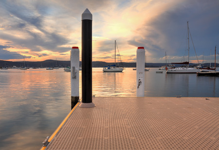 moorings: Boats and yachts moored at sunset from New Brighton Public Wharf, Saratoga, NSW Australia Stock Photo