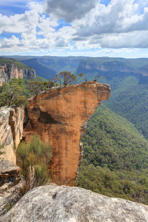 View of Hanging Rock from Baltzer Lookout, Blackheath in the Blue Mountains NSW Australia. Hanging Rock is detached from the main cliff face by a vertical crack of about half to one meter across and Hanging Rock isvery narrow about 1 metre wide
