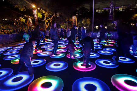 interacts: SYDNEY, NSW, AUSTRALIA - JUNE 2, 2014; The Pool at Vivid Sydney   Many interactive circular platforms sit side by side  Each is independent and simultaneously interacts with its environment, adjusting its output according to participants movements  It sen