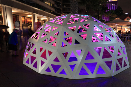 onlooker: SYDNEY NSW, AUSTRALIA - JUNE 4, 2014;   People interacting and observing the Geodesic Light Dome  Circular Quay Sydney during Vivid Sydney Festival of Light Music and Ideas   Strips of light, built into the structure will form waves of colour and light th Editorial