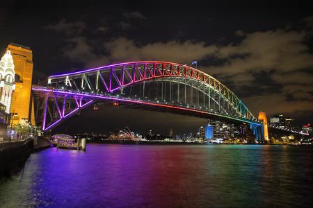 rainbow bridge: NTH SYDNEY, AUSTRALIA - JUNE 6, 2014;  Sydney Harbour Bridge in vibrant rainbow colours during the Annual Vivid Festival, view to Opera House and Circular Quay