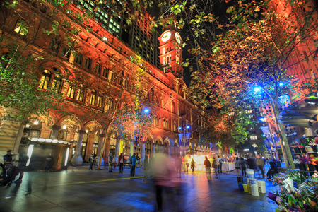 SYDNEY, AUSTRALIA - JUNE 6, 2014;   Martin Place, A CBD and shopping disrict of Sydney lit up in various ever changing colour, during annual Vivid festival   People in motion   Sky flower in distance