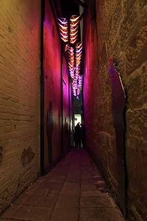 city alley: SYDNEY, AUSTRALIA - JUNE 6, 2014;  Clapiconia light installation in a narrow alleyway in The Rocks precinct during Vivid Sydney annual festival event.  The lights react and change colour to participants clapping sounds