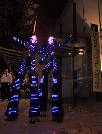 stilts: SYDNEY, AUSTRALIA - JUNE 6, 2014;  Illuminated stilt walkers wearing led light costumes at The Rocks district, for Vivid Sydney annual festival of light, music and ideas