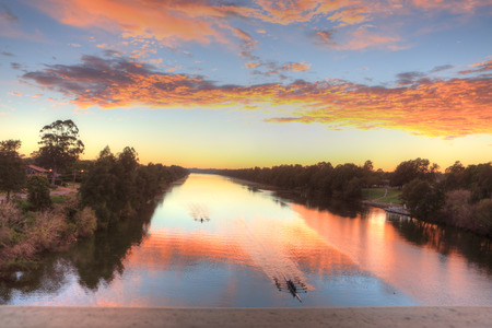 stir up: Beautiful sunrise over the Nepean River, Penrith NSW, Australia. Kayakers practice early morning before larger watercraft stir up the waters