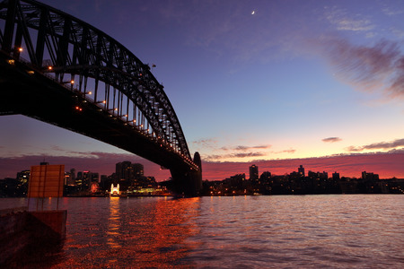 skie: View across Sydney Harbour with Sydney Harbour Bridge arching across to North Sydney and a crescent moon and rich red dawn sunrise skies forming behind silhouetted buildings on the foreshore... Stock Photo