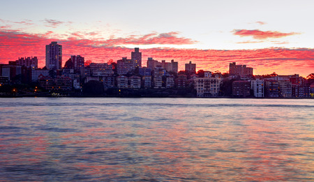 resemble: Rich red dawn sky over Kirribilli buildings and Sydney Harbour.  The rippled clouds resemble water Stock Photo