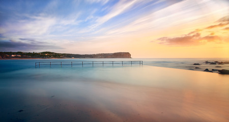 australia landscape: Sunrise at Macmasters beach pool awash with ocean swell at high tide