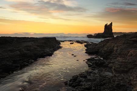 Waves crashing around Cathedral Rock at sunrise, south coast, NSW, Australia photo