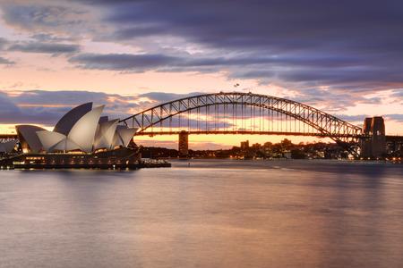 Sydney, Austrálie - 12. července, 2014; Sydney Harbour Bridge a Opera v Sydney při západu slunce Dlouhé expozice