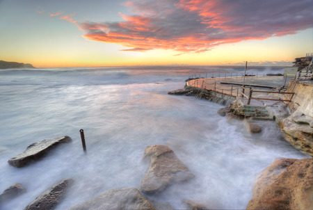 tasman: The wild ocean surging and swriling over rocks on the coast at Bronte Beach, NSW, Australia