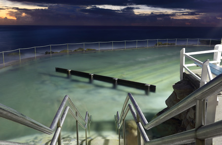 hand rails: Bronte Baths, illuminated by a light before sunrse.  This pool is fed by the ocean tides and was built in 1887. Stock Photo