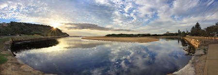 headland: Narrabeen Lakes Entrance panorama early morning with sunburst over the North Narrabeen headland.  Narrabeen surf club at right.  The lake snakes around until it meets the ocean at North Narrabeen.   Stock Photo