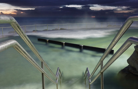 hand rails: Bronte Baths, the ocean pool at Bronte Beach Sydney.  Waves surge into the pool constantly.  Focus is to the hand rails.  Buyers this is a long 8 sec exposure taken 1 hr before sunrise at 500 iso,  there may be some grain as I did not want to overuse nois