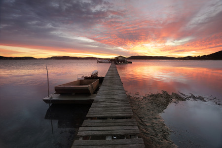 rickety: KOOLEWONG, AUSTRALIA - JULY 28, 2014; Sunrise over the Brisbane Waters with Paddys Oyster shed and rickety jetty stretching out over the waters in the Koolewong area of Woy Woy on the Central Coast.   Koolewong is aboriginal word meaning Koalas there.  T