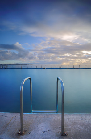 hand rails: The public ocean rock  pool at Collaroy beach.  Vertical crop.   Collaroy Rock Pool has two odd-shaped classic ocean baths with chains, including a 50-metre lap pool.    Long exposure.  Note ocean pool, not a private or commercial pool.