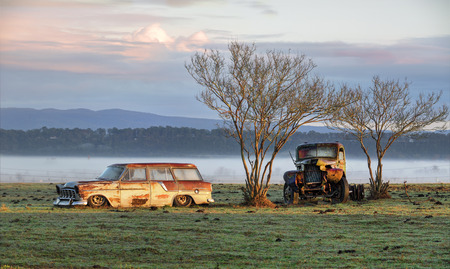 Very old vintage and rusty truck and car sit undisturbed in a field and catch the first rays of sunlight on a  misty foggy frosty morning in the country.  Richmond NSW Australia photo