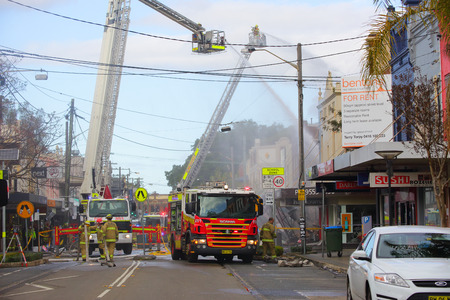 explosion engine: ROZELLE, AUSTRALIA - SEPTEMBER 4, 2014;   Firefighters on cranes douse the flames of a convenience store after an explosion.   Grave fears are held for three missing people who resided in the building upstairs.  Darling Street, Rozelle, Sydney, Australia. Editorial