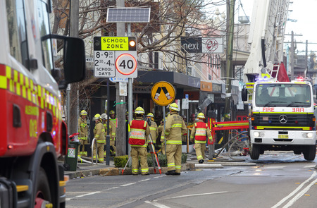 explosion engine: ROZELLE, AUSTRALIA - SEPTEMBER 4, 2014; A team of firemen and engineers at work after a shop explosion in Rozelle.