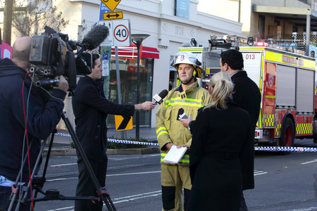 explosion engine: ROZELLE, AUSTRALIA - SEPTEMBER 4, 2014; Today Show Chris Urquhart and ABC news reporter are briefed by Superintendant Paul Johnstone of Fire and Rescue regarding the tragic explosion and fire. Editorial