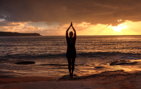 Female relaxing at sunrise, performing tadasana - mountain pose by the sea at sunrise photo
