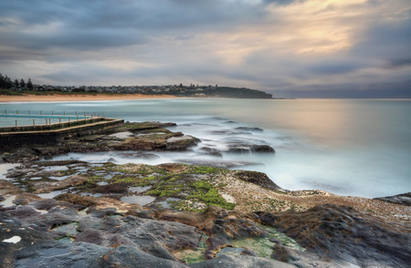 tasman: North view overlooking coast and rock pool at South Curl Curl. Australia.  Motion in water, clouds and railings Stock Photo