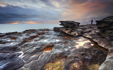 The view south from South Curl Curl rocks, NSW Australia.   The rock really grabbed my eye and this was where the most colour concentration from sunrise was warming up the stormy clouds.  A fisherman clenches fists in jubilation. photo