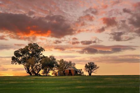 Australische outback zonsondergang. Oude boerderij, afbrokkelende muren en veranda met twee watertanks in de achtertuin ligt verlaten op een heuvel bij zonsondergang. De laatste zonnestralen die zich uitstrekt over het landschap schilderen van het gras in gevlekt licht en de rand van de tanks en het huis Stockfoto