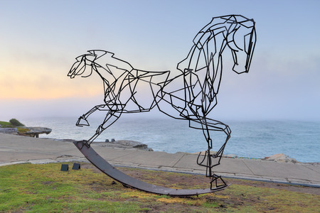 titled: BONDI, AUSTRALIA -  OCTOBER 25, 2014; Sculpture by the Sea annual free public  event 2014.  A sea fog rolls in behind the sculpture titled Which Way Forwards by  Harrie Fasher, NSW.   The double headed horse is meant for us to reflect on the opposing dire Editorial