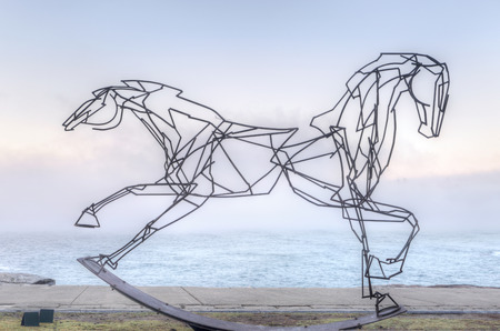 BONDI, AUSTRALIA -  OCTOBER 25, 2014; Sculpture by the Sea free public annual event 2014.  Sculpture titled Which Way Forwards by  Harrie Fasher, NSW.   A double headed horse, one side galloping, the other side in control - a look at  life  Materials, ste Editorial