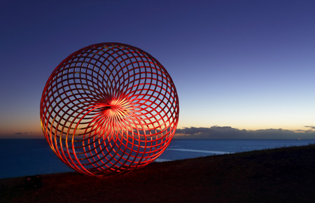 sisyphus: BONDI, AUSTRALIA -  OCTOBER 29, 2014; Sculpture by the Sea Annual Event 2014.  Sculpture titled Sisyphus by George Andric, SA.  Lightpainted with a torch for a red glow.  Materials, stainless steel.  Price $36000