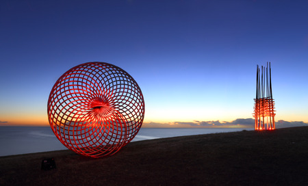 sisyphus: BONDI, AUSTRALIA -  OCTOBER 29, 2014; Sculpture by the Sea Annual Event 2014.  Sculpture titled Sisyphus by George Andric, SA.  Lightpainted with a torch for a red glow and Save Our Souls by Cave Urban lit up by red LED lights in background..
