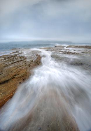 baratro: Misty nebbia nasconde il cielo e turbolento oceano flussi abisso di roccia