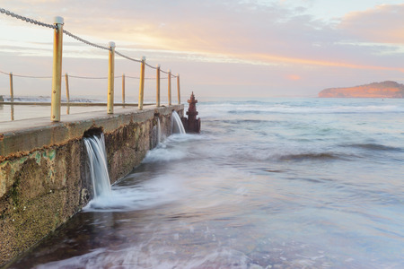 The Overflow.   Ocean water overflows at Mona Vale Ocean Rock Pools.  A sea mist softens the colours and contrast.  Taken early morning just after sunrise.